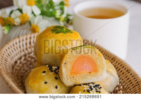 Delicious Chinese pastry or mooncake filled with mung bean paste and salted egg yolk on wood basket. Mooncake or Chinese pastry served with tea on wood table in side view close up. Homemade bakery concept of Chinese pastry.