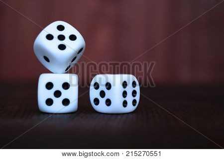Heap of three white plastic dices on brown wooden board background. Six sides cube with black dots. Numbers 1 3 5 6.