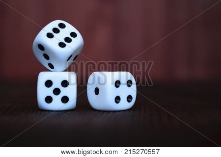 Heap of three white plastic dices on brown wooden board background. Six sides cube with black dots. Numbers 1 2 3 4 5 6.