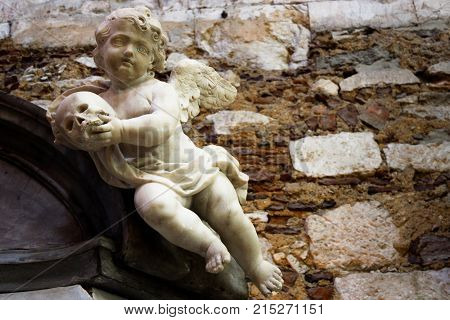 A statue of a cherub holding a skull at The Convent of Our Lady of Mount Carmel. Lisbon Portugal.