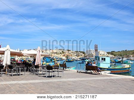 MARSAXLOKK, MALTA - APRIL 1, 2017 - Traditional Maltese Dghajsa fishing boats in the harbour with waterfront buildings to the rear and restaurants on the quayside Marsaxlokk Malta Europe, April 1, 2017.