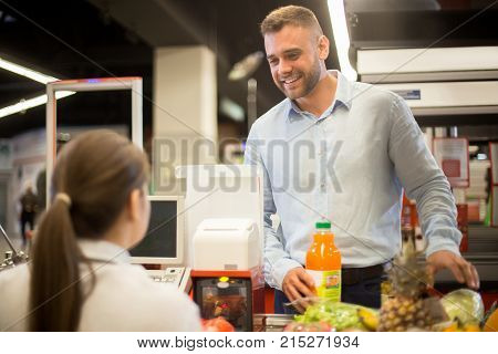 Portrait of handsome young man buying food in supermarket smiling happily at cashier scanning prices