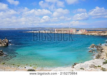 PARADISE BAY, MALTA, APRIL 2, 2017 - Rocky coastline with hotels and ferry terminal to the rear Paradise Bay Malta Europe, April 2, 2017.