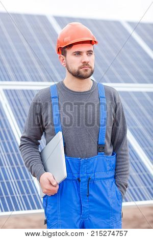 A serious worker at the solar battery station with a beard, dressed in a blue uniform and an orange helmet, keeps a modern tablet on hand and looks somewhere with a serious look. Outdoors.
