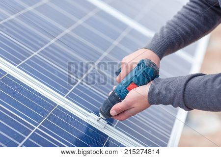 The hands of the solar battery station worker in the uniform drills the solar battery panel by the drill. Close-up. Outdoors.