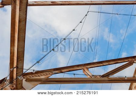 Overhead rusted steel trusses and strings of light before a blue sky with clouds horizontal aspect