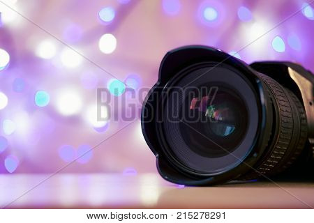 The camera lens is on a background of bright New Year's lights