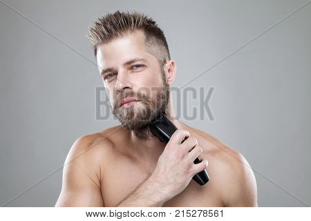 Handsome young bearded man trimming his beard with a trimmer poster