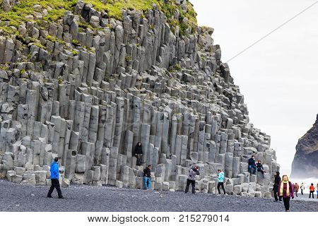 People Near Wall Of Reynisfjall Mount In Iceland