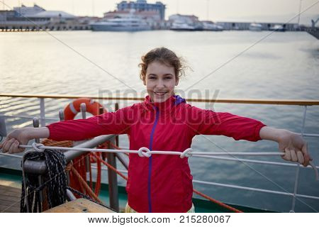 Girl in red jacket holds rope with three knots on ship deck.