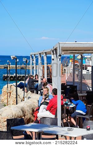 MELLIEHA, MALTA - APRIL 2, 2017 - Tourists relaxing at a pavement cafe in the harbour Mellieha Malta Europe, April 2, 2017.