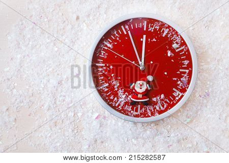 Red wall clock isolated on white background. The clock shows the last minutes before the new year. The clock lies on the snow