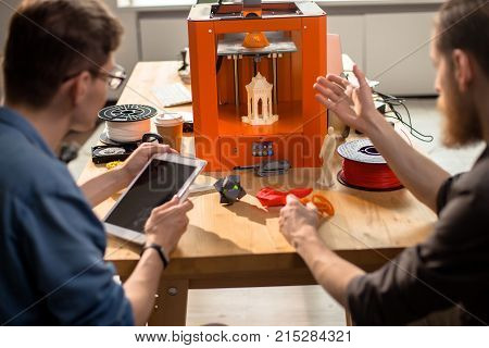 Back view of talented young engineers sitting at desk and carrying out quality inspection of prototype made with help of 3D printer, interior of modern lab on background