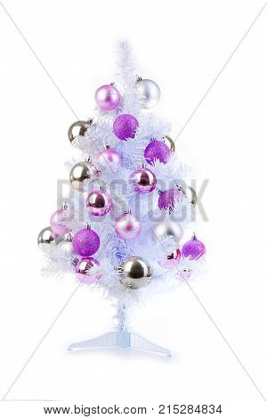 White christmas tree with silver and pink baubles ornaments. Pink rose and silver christmas ball ornament on white faux artifial christmas tree. Isolated studio photo.