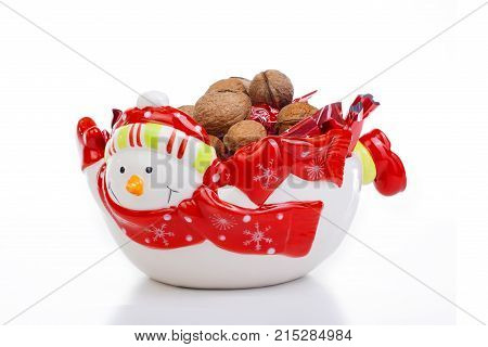Christmas decoration. Snowman plate with candy and walnut on isolated white studio photo. Cute.