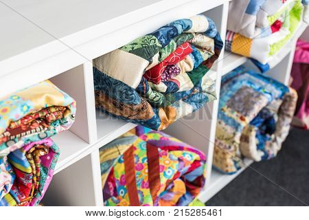patchwork, sewing and fashion concept - colorful finished quilts in the studio at white shelves with few storage compartments, the warehouse of finished products, side view, selective focus