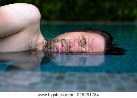 Caucasian man is afraid to swim in swimming pool. He do not like chlorine water and closes his eyes with emotion of disgust on the face
