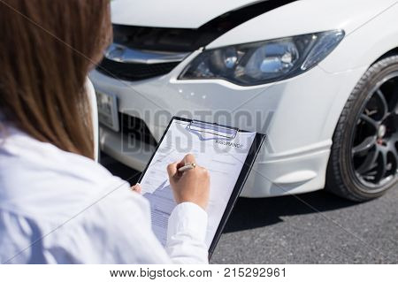 Side view of writing on clipboard while insurance agent examining car after accident
