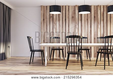 White and wooden dining room interior with a long wooden table black chairs and an original door. 3d rendering mock up