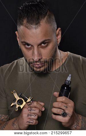Latin tattoo artist portrait on black background.