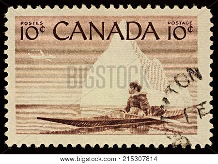 Moscow Russia - November 23 2017: A stamp printed in Canada shows Eskimo in a kayak on iceberg background series