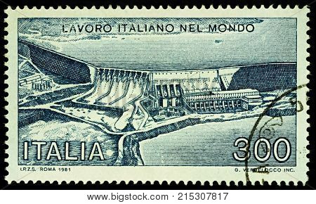 Moscow Russia - November 24 2017: A stamp printed in Italy shows large dam on the river with hydroelectric power station series