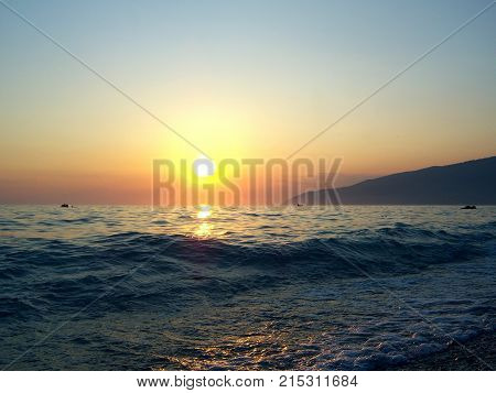 Bright bright sun. Calm sea. Not large waves roll on a gentle beach and roll back into the sea. Over the sea after a hot day hangs a thick haze. The rays of the sun in the haze turn red. In the distance a mountainous shore overgrown with forest is visible