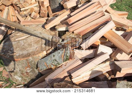 axe in log stack of firewood. Axe ready for cutting timber. pile of firewood logs and blocks