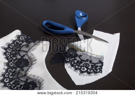 Sewing And Dressing. On The Dark Surface Is A White Dress With A Black Ribbon Sewn For Decoration. N