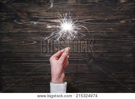 New year party burning sparkler closeup in female hand on black background. Woman holds glowing holiday sparkling hand fireworks, shining fire flame. Christmas light.