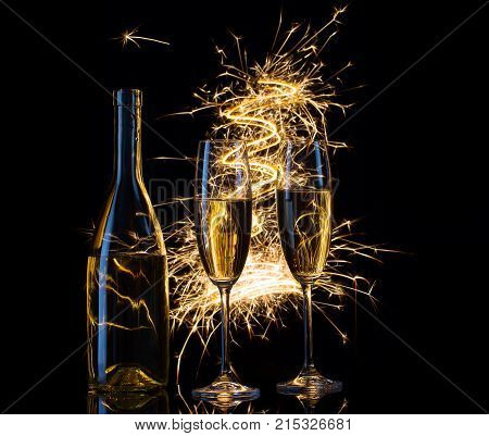 Festive champagne in the sparks of lights. Black background. The concept of celebrating Christmas or a wedding.