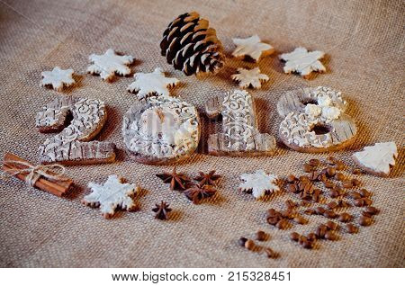 Wooden new year numbers 2 0 1 8 with pine cone aniseed cinnamon sticks and coffee beans on brown sackcloth background