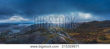 Unidentifiable tourists standing on the top of mount Ulriken in Bergen in loving embrace, Norway
