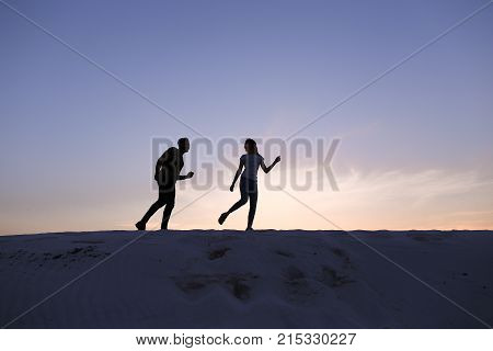 Beautiful lovers, young Arab man with guitar in hand and European woman of woman happily spend their free time laughing and smiling, downloading and running through sandy hills of desert against blue sky at sunset on warm summer evening. man with dark hai