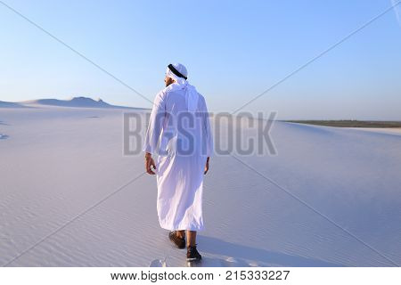 Charming young male Arab looks toward sun and goes up sand, examining landscapes of wide desert. Muslim smiles, leans over and takes sand in hands, blowing in wind. Swarthy, handsome Muslim with short dark hair dressed in kandura, long, spacious dress mad