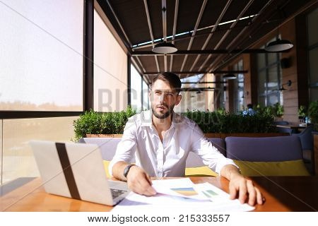 Lucky successful manager working with laptop and documents with diagrams at table indoors. Young gladden man enjoying good job and result, looking at cam and gesticulating yes.