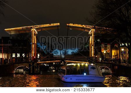 Amsterdam, Netherlands - January 14, 2017: Illuminated drawbridge by night in Amsterdam seen from the water