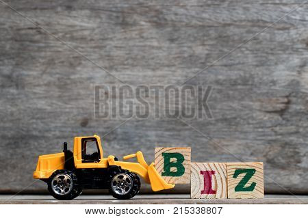 Yellow plastic bulldozer hold letter B to complete word BIZ (Abbreviation of business) on wood background