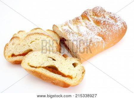 The rich ruddy roll is strewed by powdered sugar with a stuffing from dried apricots on a white background