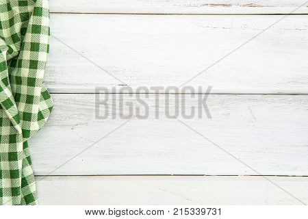 Crumpled green checkered tablecloth or napkin on empty white wooden table with copy space for food cooking menu background concept top view or overhead shot