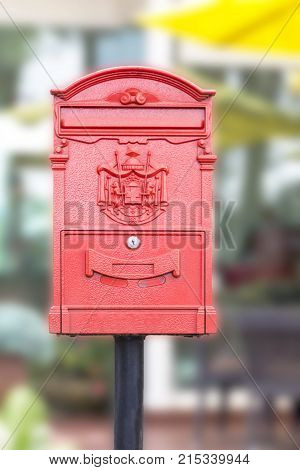Red mailbox in front of a house. Mailbox made of metal.