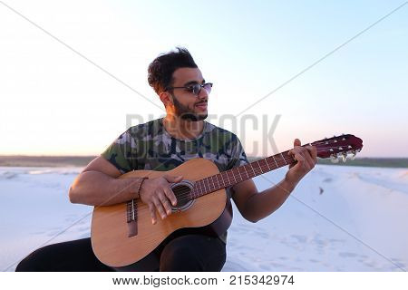 Ambitious budding musician, Muslim guy performs lyrical melody on musical instrument and guitar, and raises skill of professionalism, sitting on sandy hill in middle of wide sandy desert on warm summer evening at sunset.