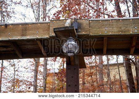 Old light hanging from wooden platform outside