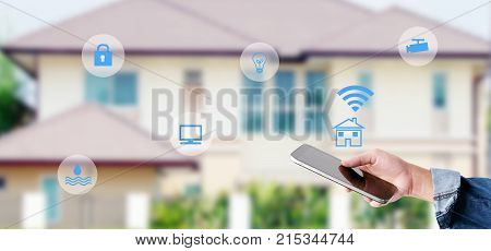 Hand using smart phone as smart home control application over blurred house background banner smart home concept