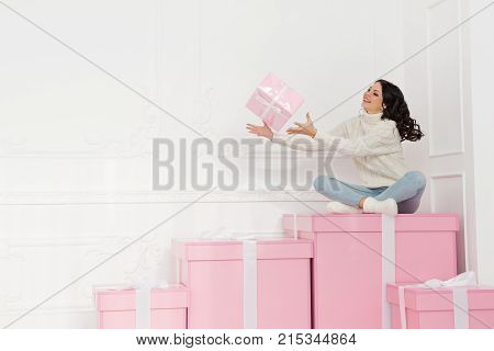 Young cute teenage girl in a knitted white sweater and socks. She catches a pink box with a gift. Holidays. Happy New Year. Merry Christmas. Valentine's Day. Birthday.
