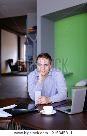 Handsome and self-assured guy, manager of company pondered and stares into distance in front of him, leaning head against hand, laughing and smiling, holding gadget in hands and sitting at table with laptop and tablet with cup of coffee in modern office i