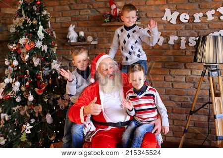 Happy male children and Christmas grandfather posing smiling at camera. boys cheerfully wiggle their hands Santa Claus shows gesture with thumb up