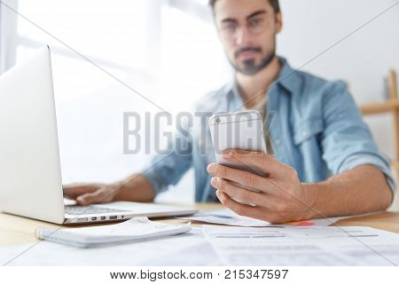 Modern Smart Phone In Man`s Hands. Young Hipster Guy With Beard Monitors News For Website Uses Mobil