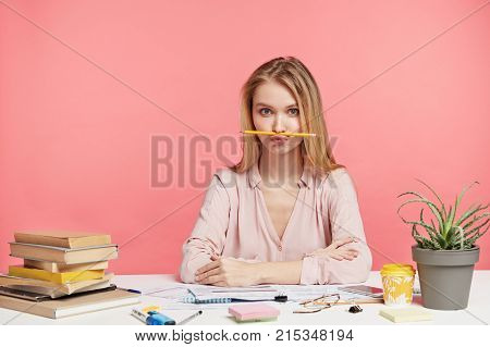 Horizontal Portrait Of Funny Female Student Keeps Pencil On Mouth, Foolishes After Long Prepareation