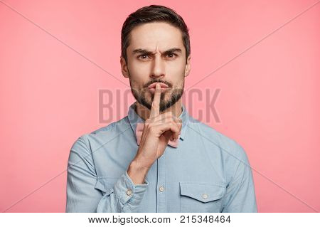 Confident Serious Male Dressed Formally, Keeps Index Finger On Lips, Asks Best Friend To Be Quiet An